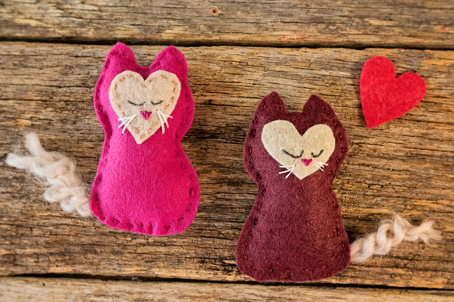 two hand sewn felt kittens together with a felt hear cut out