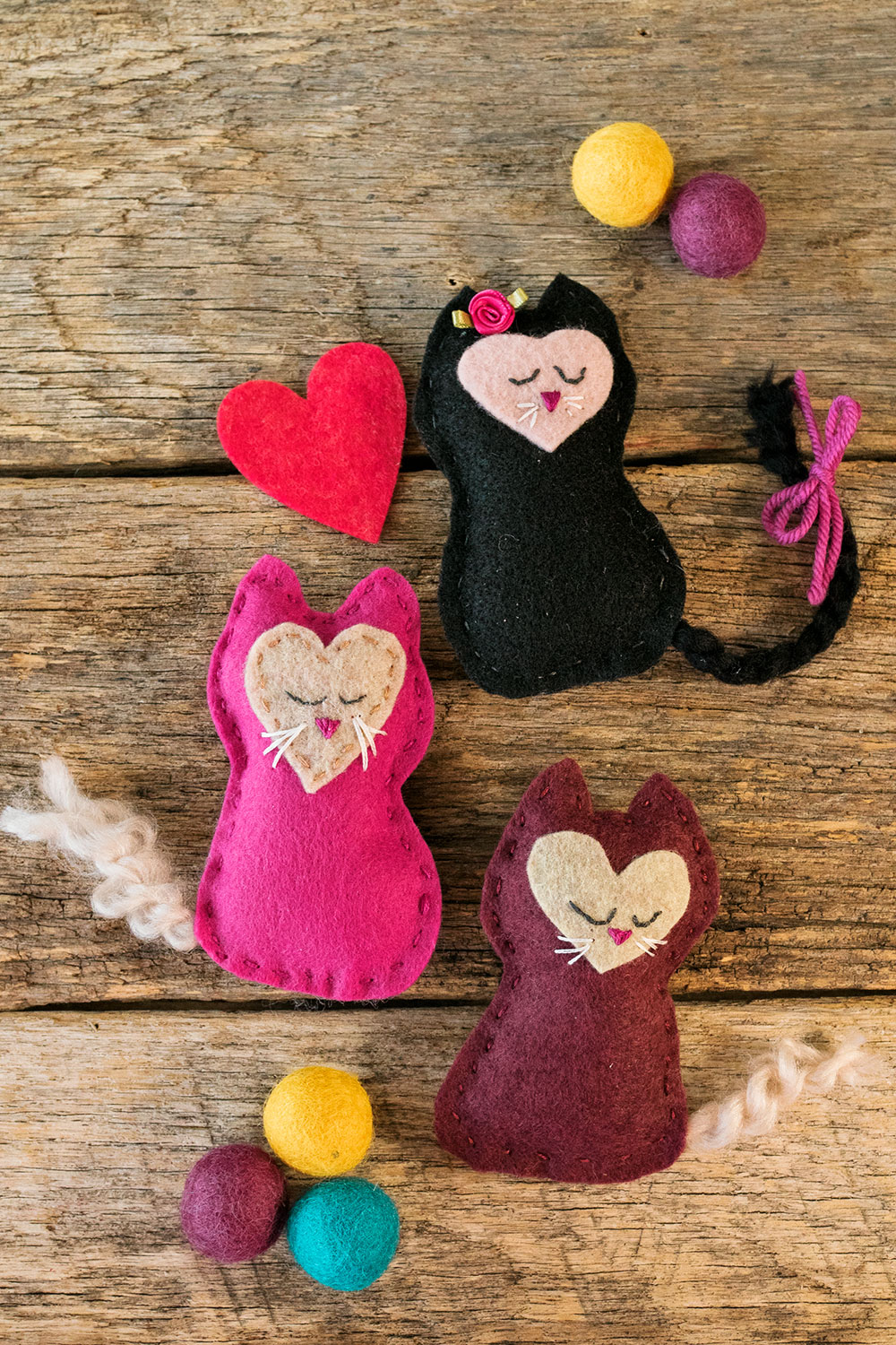 A collection of three small kitten toys hand sewn from felt posed with a felt heart and wool felted balls