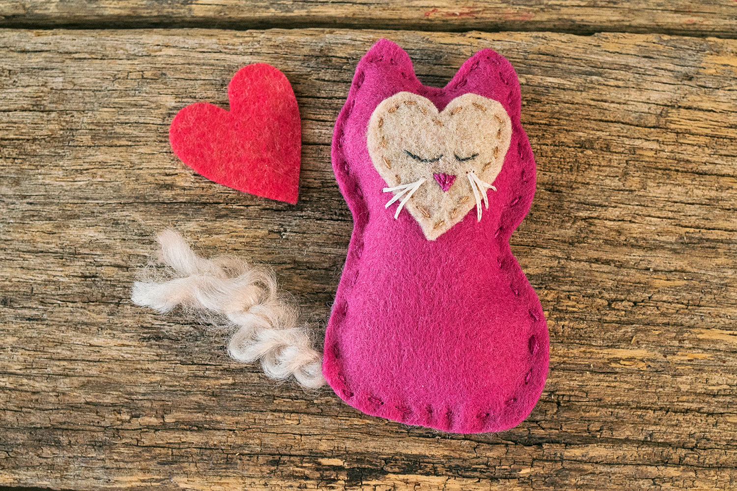 closeup of a handstitched felt kitten toy with a felt heart cut out