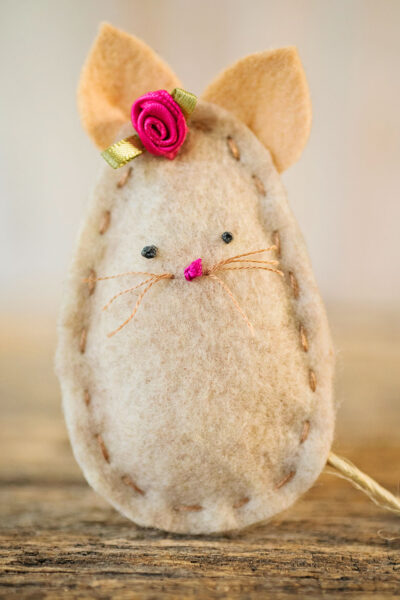 close up view of a hand stitched felt mouse with a pink rose ribbon bow. The eys and nose are stitched on using french knots and the mouse has cut whiskers
