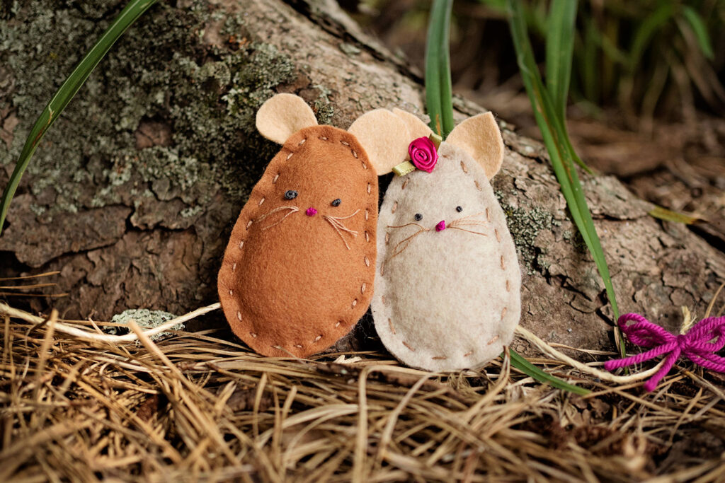 Two hand stitched felt craft mice posed together in pine straw at the base of a tree