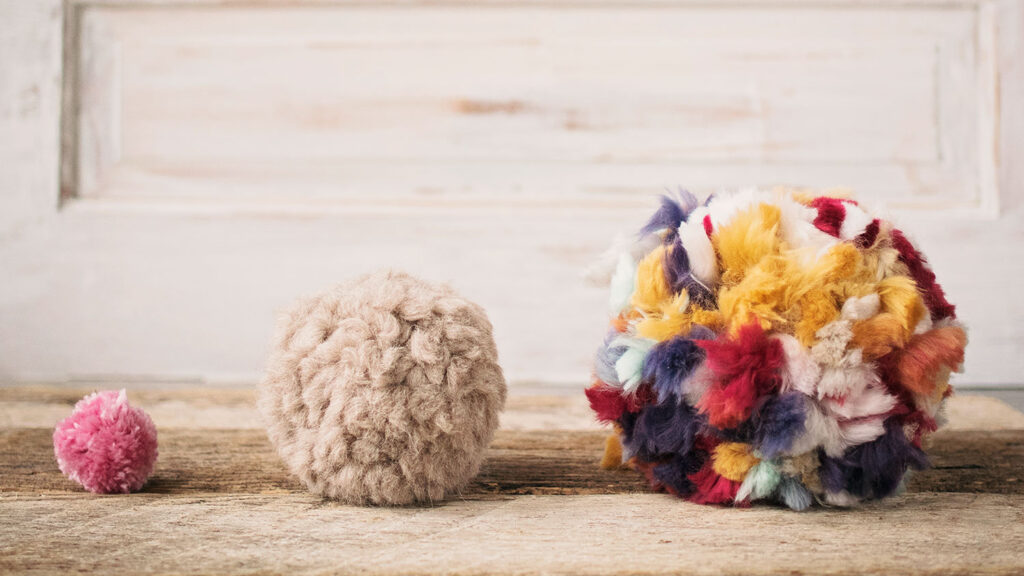 3 pom poms are lined up from smallest to largest
