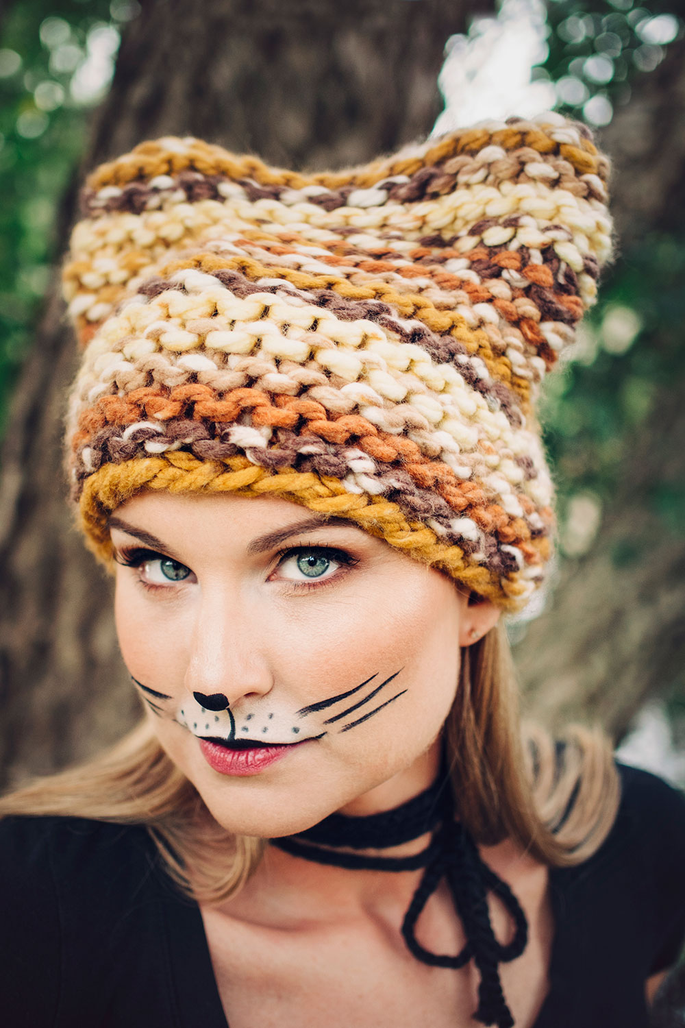 beautiful blonde model wearing makeup to look like a cat in a brown and golden chunky knit hat with ears