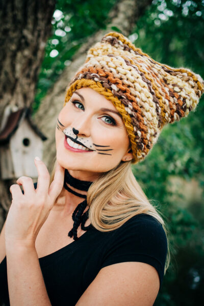 Smiling womans wears a multi colored knitted cat hat with cat makeup