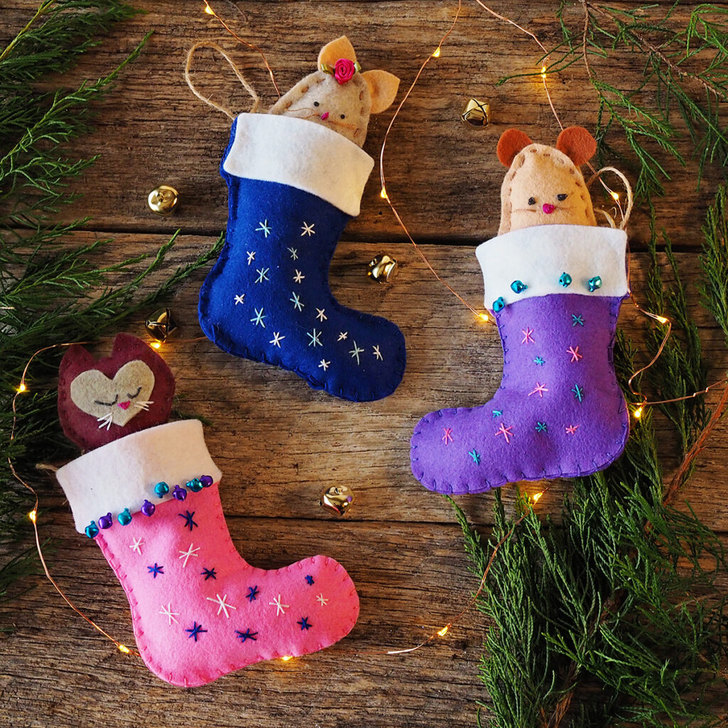 overhead view of three hand sewn felt stockings with 2 mice and a cat felt toys posed on barn wood with greenery and fairy lights
