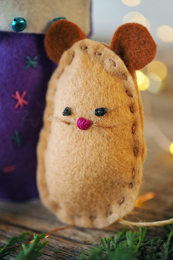 close up on a hand stitched felt mouse with fairy lights in the background and next to a hand stitched Christmas stocking