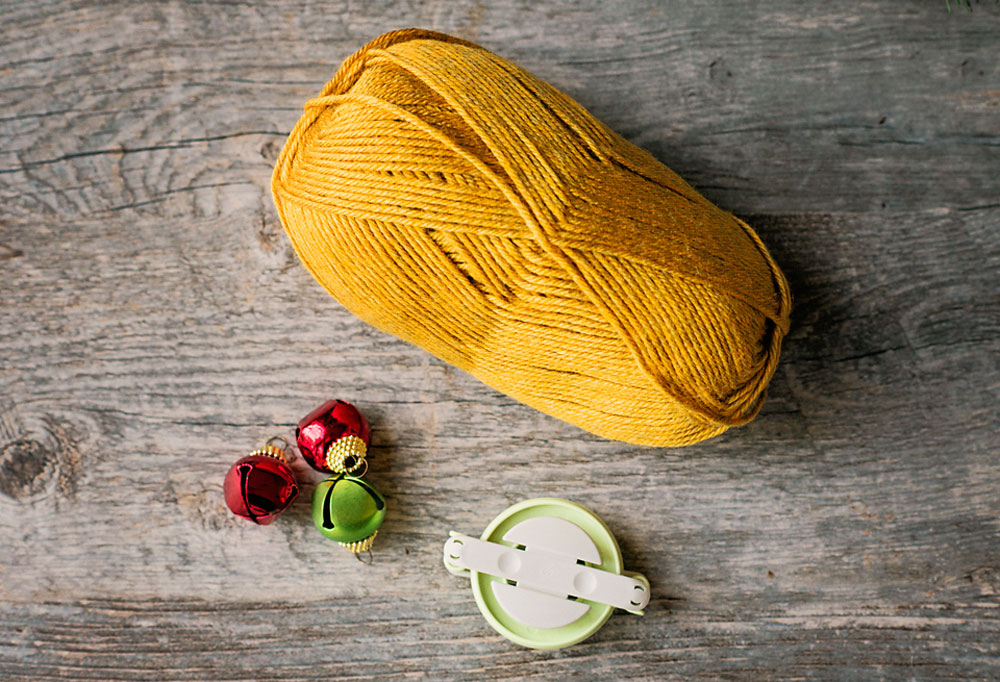 golden yellow yarn with a medium pom pom maker