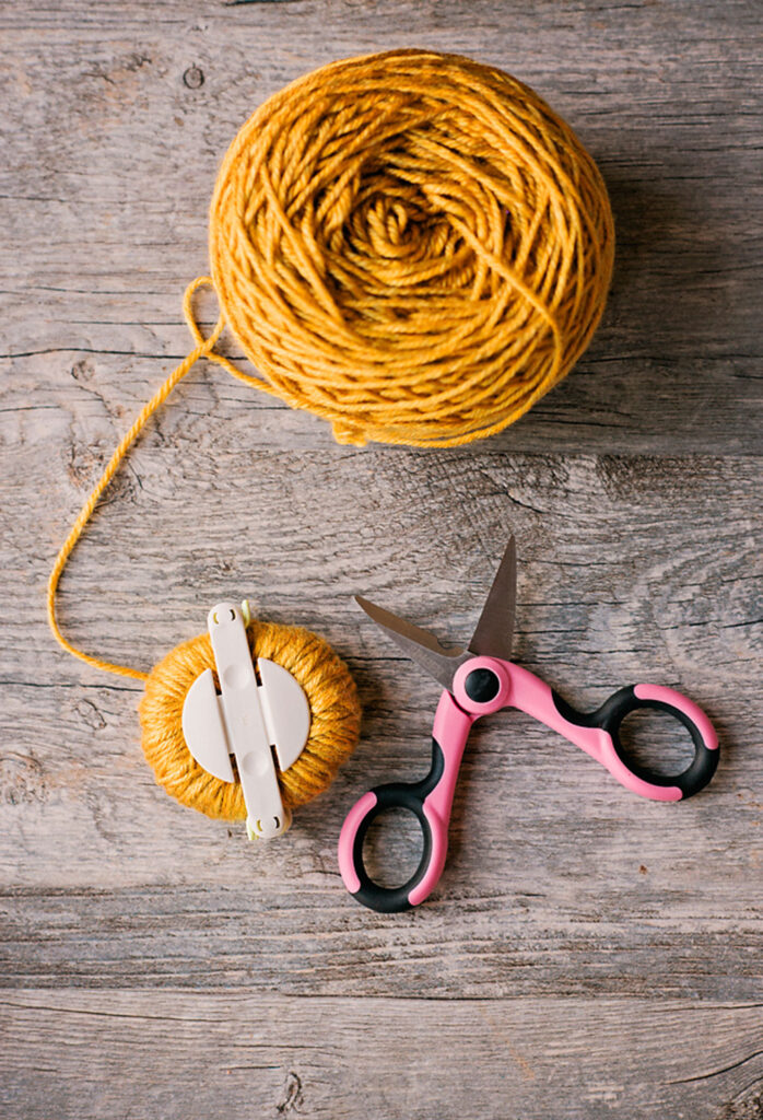golden yellow yarn with a medium pom pom maker posed with pink scissors
