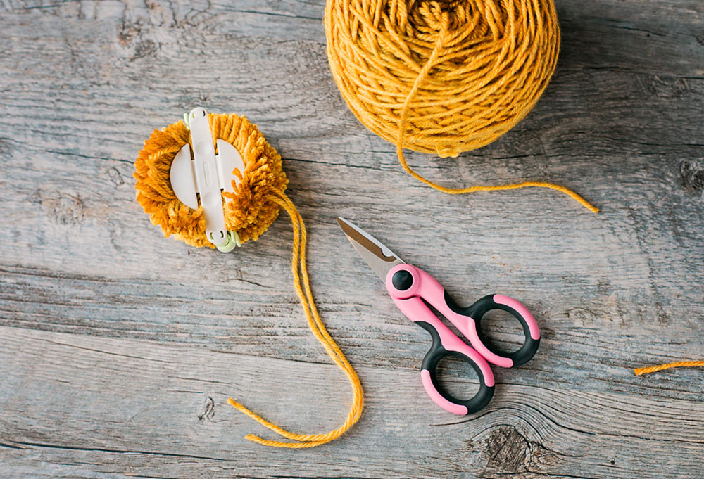 golden yellow yarn with a medium pom pom maker with fully cut yarn wraps and scissors