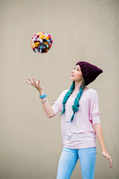young model with blue hair tosses a jumbo pom pom in the air and it looks like it's floating