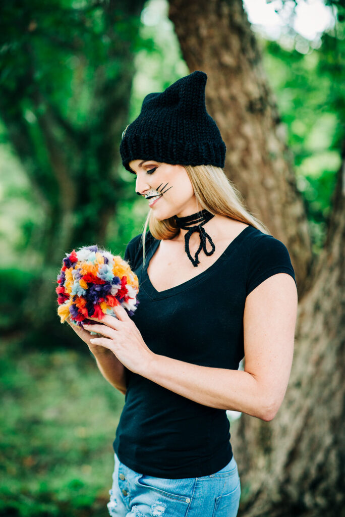 A blonde model in a black hat with cat makeup is holding a multi color jumbo pom pom