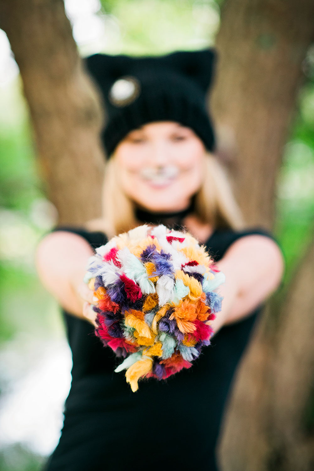 model holds jumbo multi colored pom pom in front of her