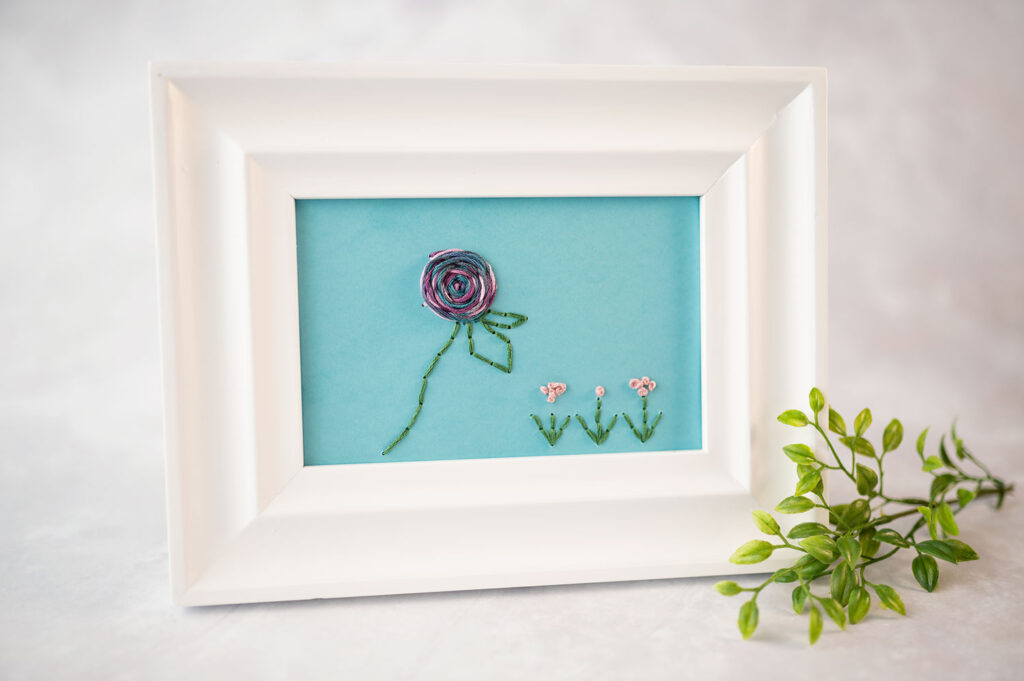 Hand stitched picture on card stock is in a frame. The frame is white and the picture is blue paper with 4 flowers stitched using embroidery