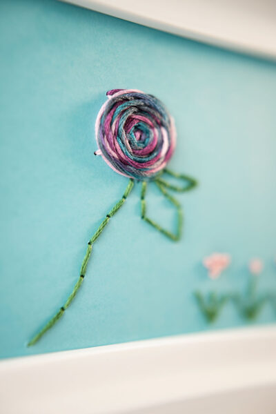 closeup view of the woven wheel rose and back stitch stem