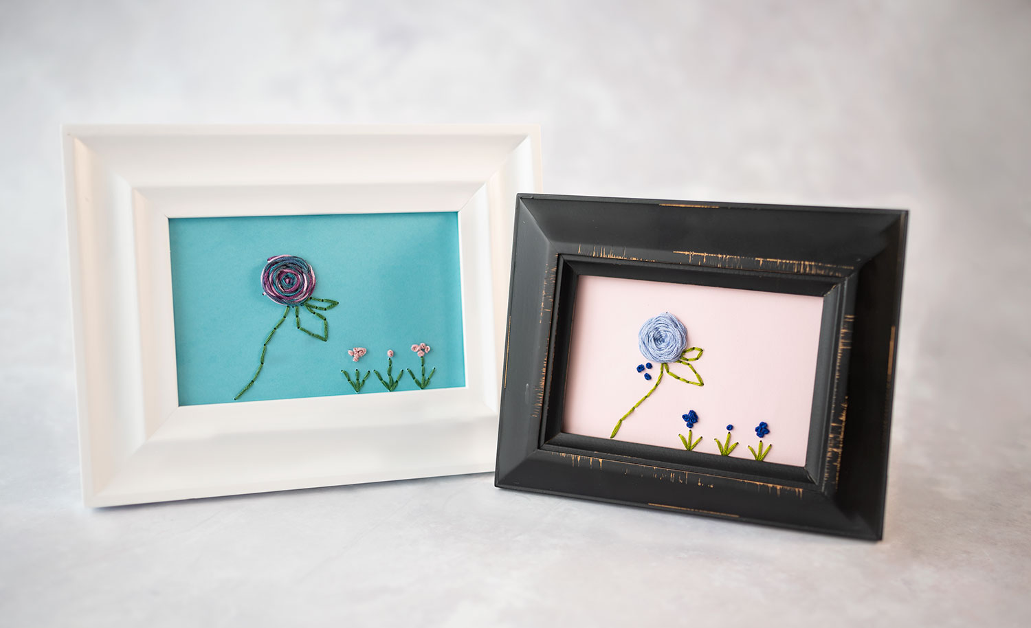 two framed, hand stitched flower designs. One in a white frame and one in a black frame. Both are hand stitched using the included pattern.
