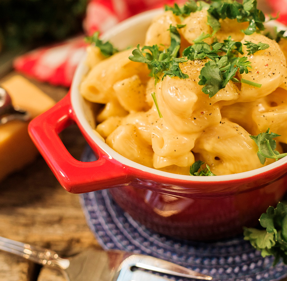 Close up view of a red dish filled with creamy golden macaroni and cheese garnished with chopped parsley