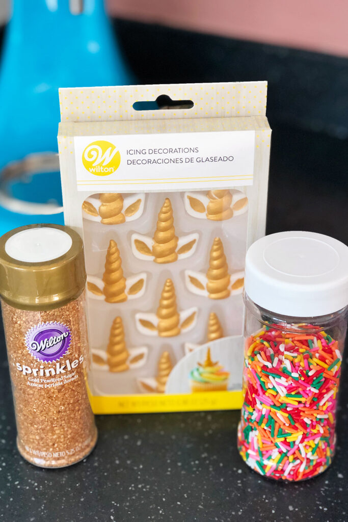 a bottle of gold sanding sugar sprinkles, a bottle of rainbow jimmies and a package of unicorn styled icing decorations