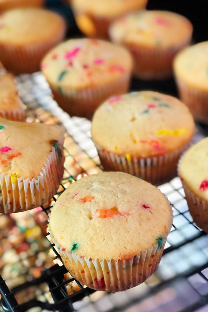 Unfrosted vanilla cupcakes filled with multicolor sprinkles cooling on a baking rack