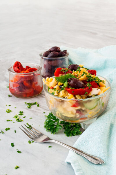 clear bowl with colorful tortellin salad with brigh green parsely scattered about