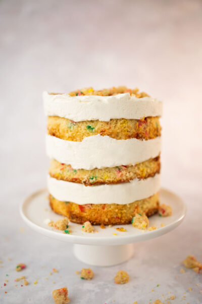 Side view of the a very tall layer cake frosted with fluffy, white frosting and decorated with a colorful rainbow crumb topping