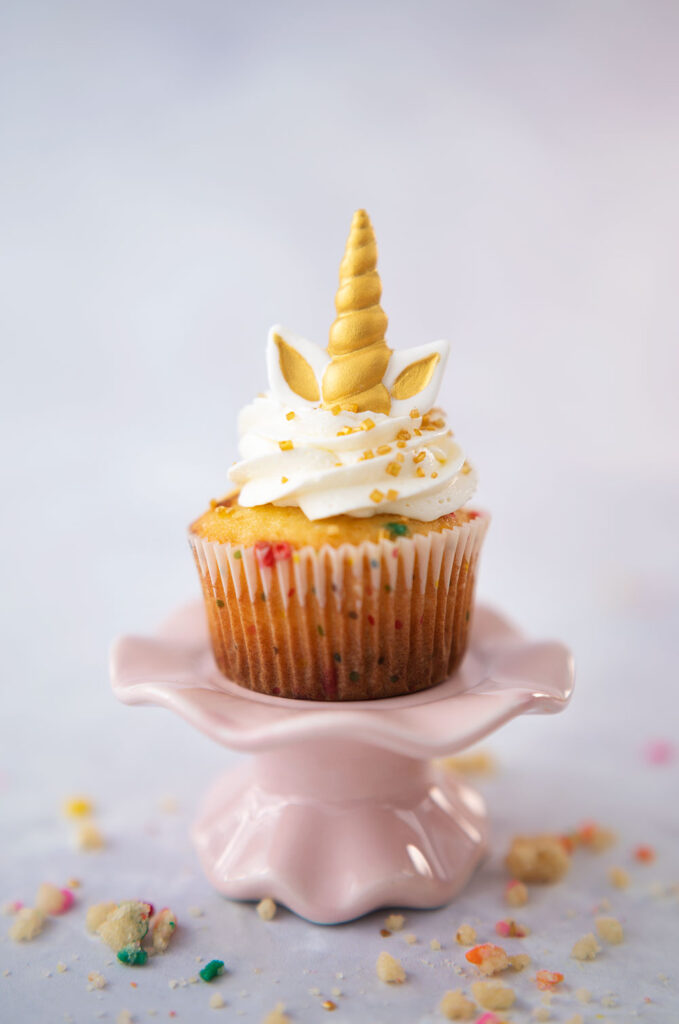 closeup of a vanilla cupcake with a polka dot wrapper and toppe with cloud white frosting and unicorn horn and ears