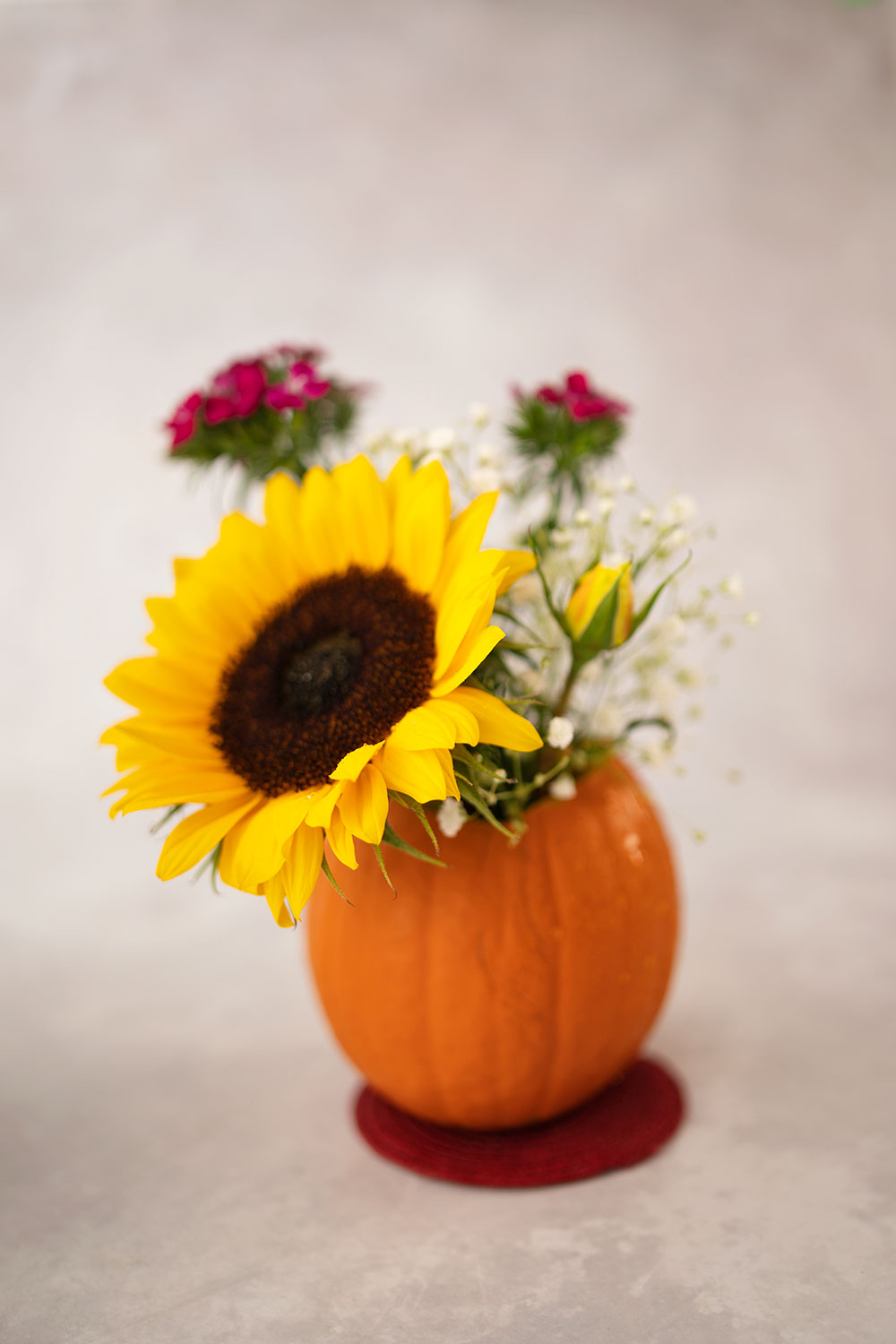 small pumpkin used like a vase and has a sunflower and a yellow rose with smaller flowers