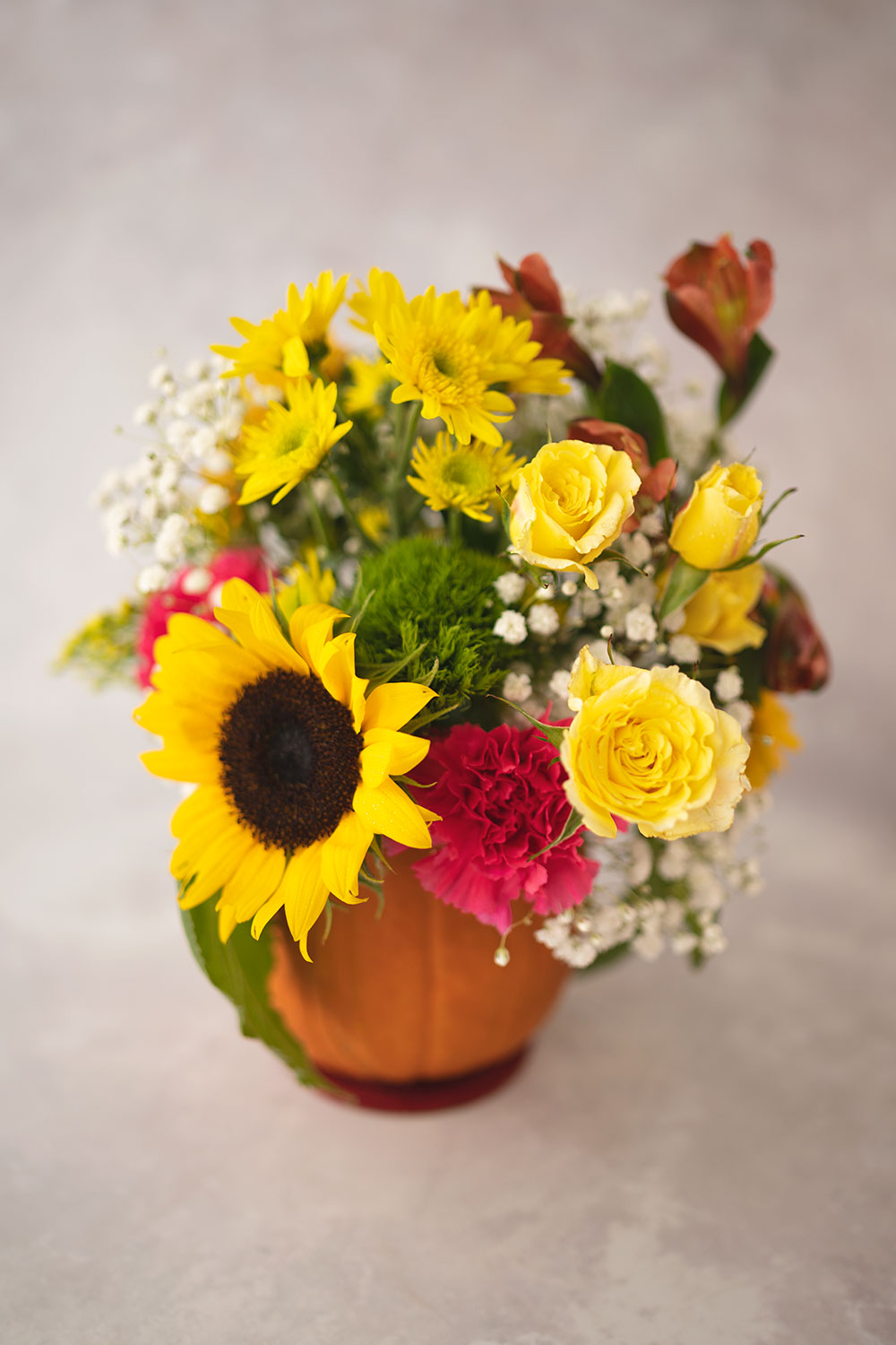 closeup of mostly yellow fresh cut flowers in a fall floral arrangement