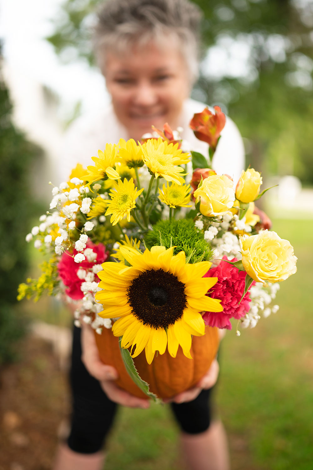 smiling woman holds a large pumpkin filled with fresh cut flowers in front of her