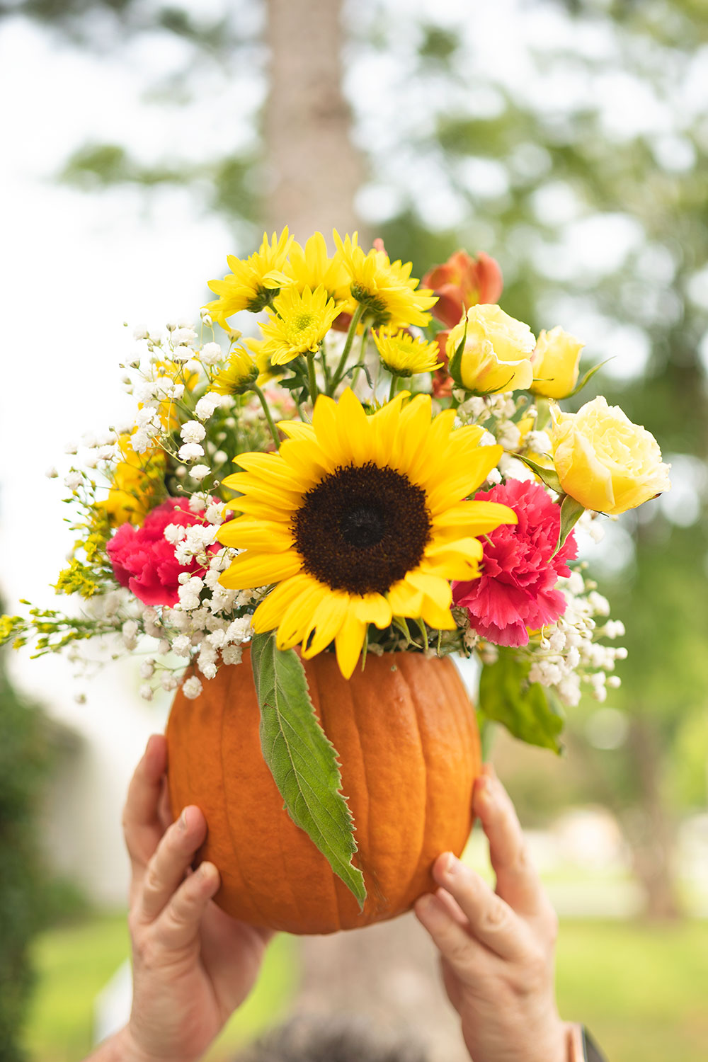 Hands holding a pumpkin with fresh flowers coming out its top