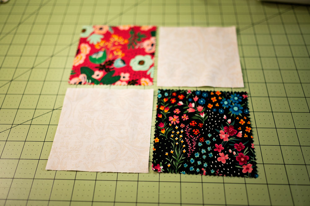4 squares of fabric laying in 4 patch formation on a green cutting mat