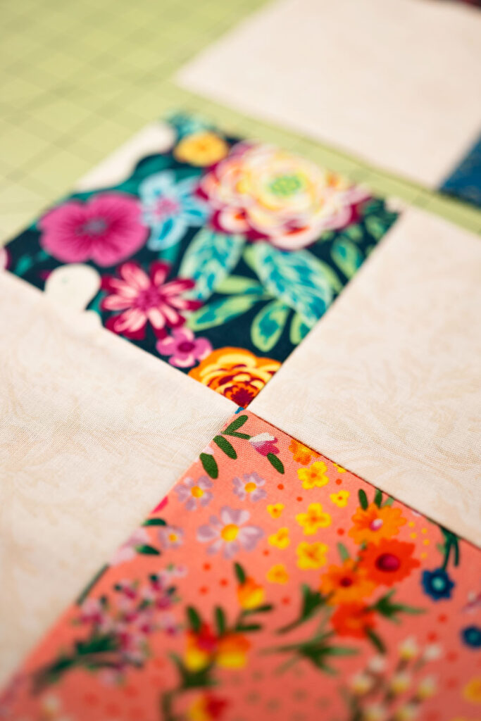 two colorful fabrics meet at a corner point in a quilt block