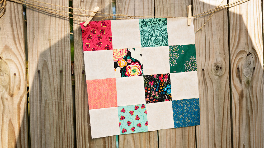 a small patchwork quilt hangs on a piece on twine on a rustic fence