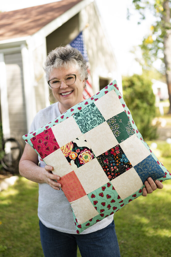 smiling woman hold an over sized patchwork pillow