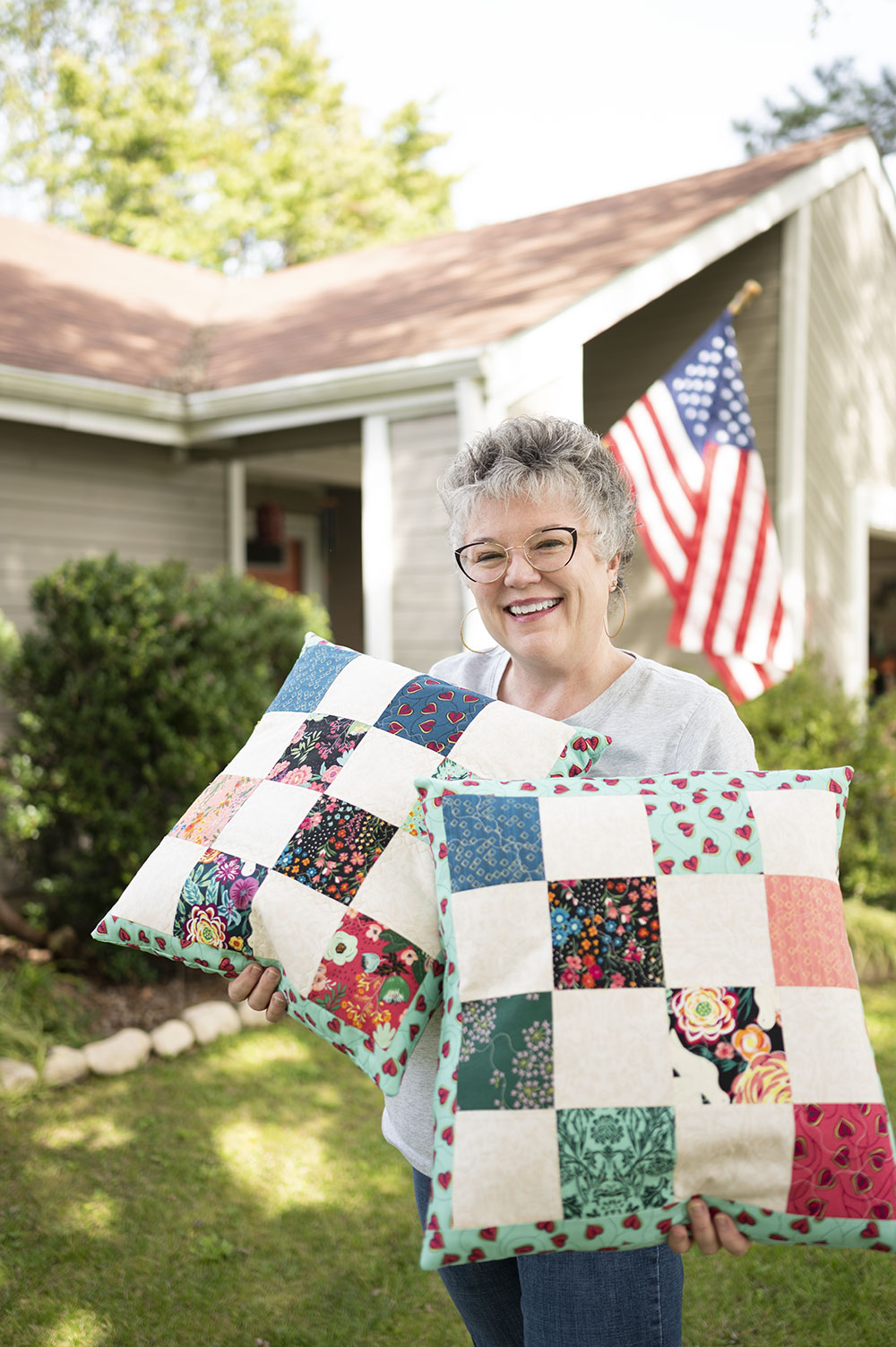 Smiling woman holds two large patchwork pillows in her front yard