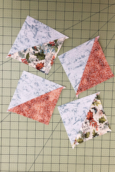 4 half square triangles on a cutting mat