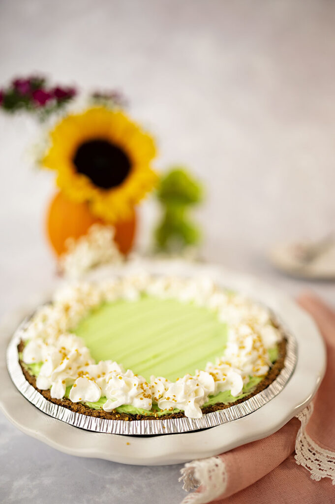 a beautiful green pie with dollops of white whipped cream piped in stars all the way around the edges.