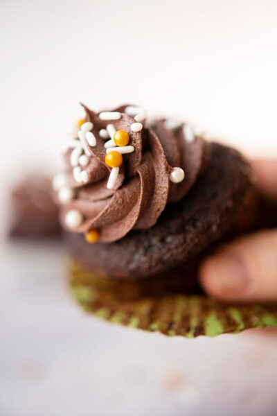 a hand holds a chocolate cupcake with the wrapper peeled back
