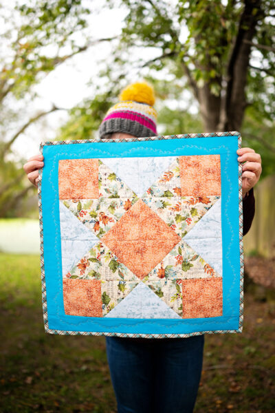woman holds color mini quilt