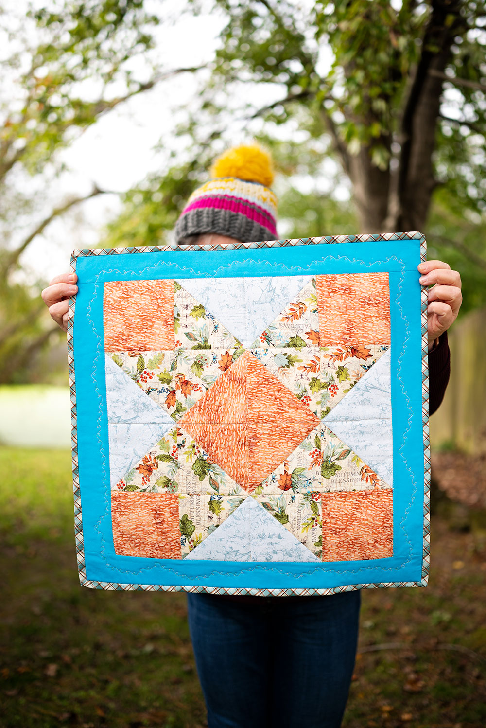 woman holds the completed mini quilt project showing off the ribbon star design