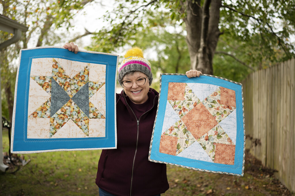 smiling woman holds two similar star block patterns