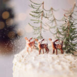 powdered sugar snow on deer miniatures on top of a white cake