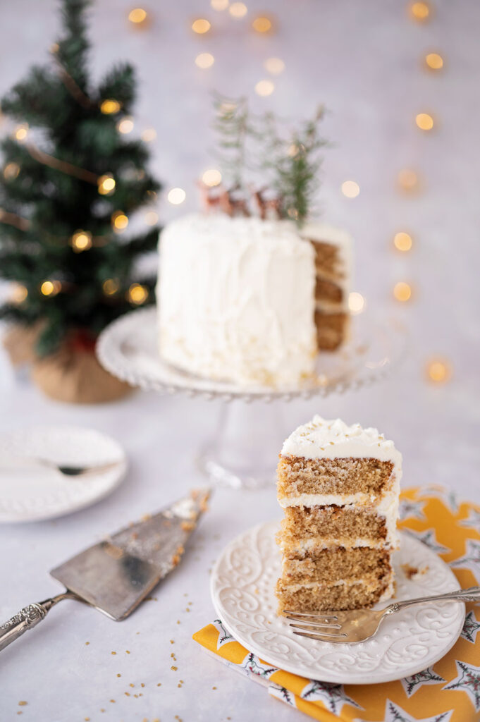 styled scene with a tall slice of Christmas cake with sliced cake in the background