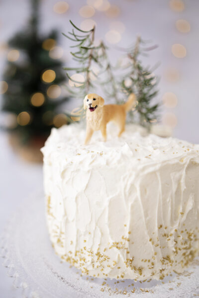 White cake with golden retriever miniature on top for a decoration