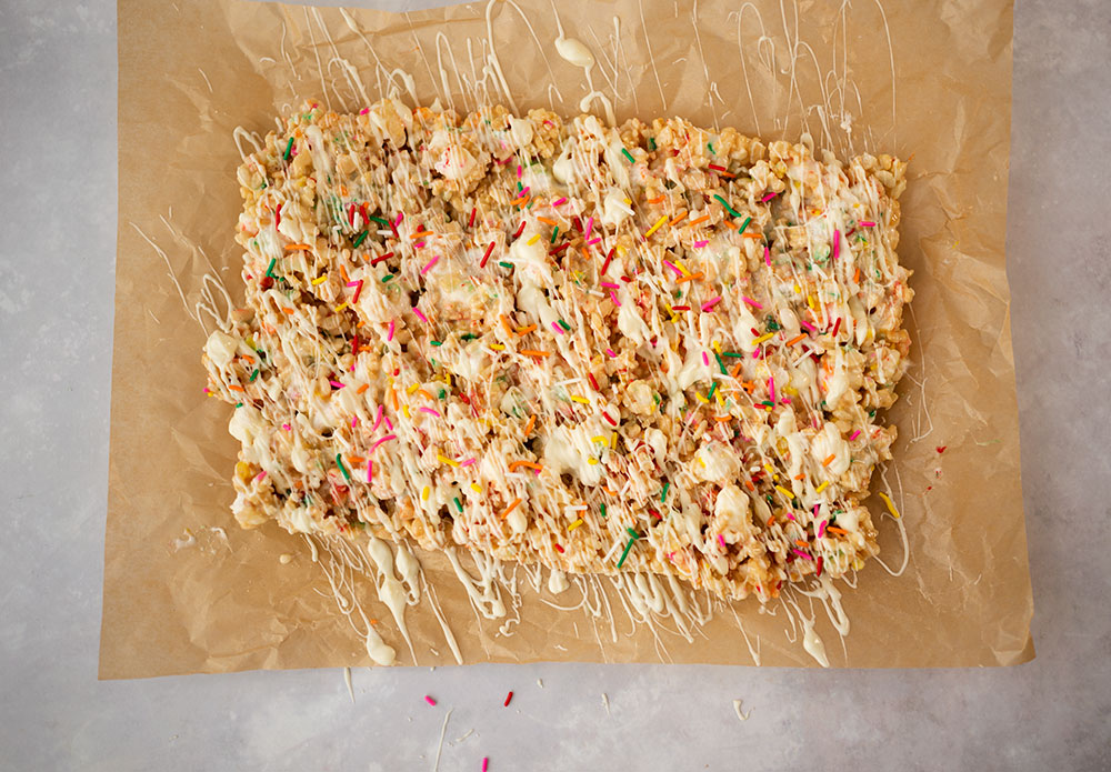 overhead view of cooled rice krispies treats with white chocolate and sprinkles