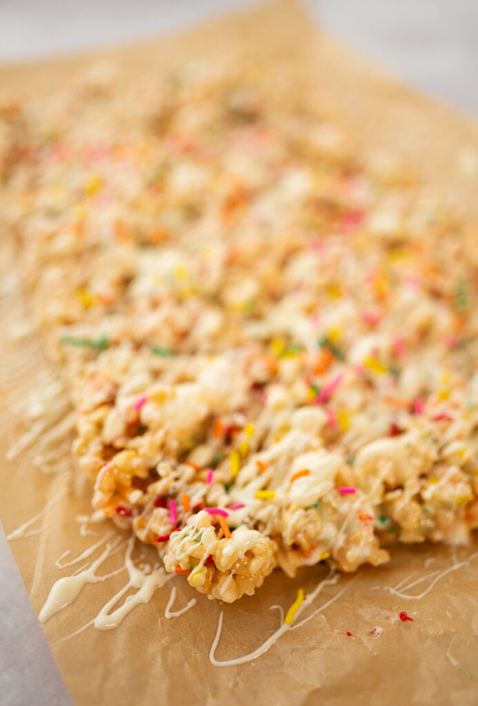 close up of a corner piece of fancy rice krispies treats topped with white chocolate and sprinkles