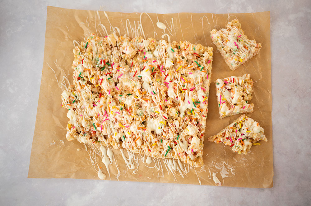 over head view of cut rice kripsies treats topped with white chocolate and sprinkles