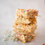 close up of a stack of cut rice krispies treats with colorful sprinkles