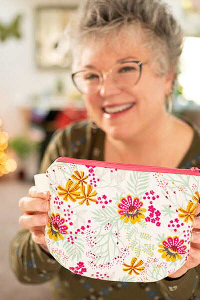 Smiling woman holds a floral printed zipper bag with a hot pink zipper