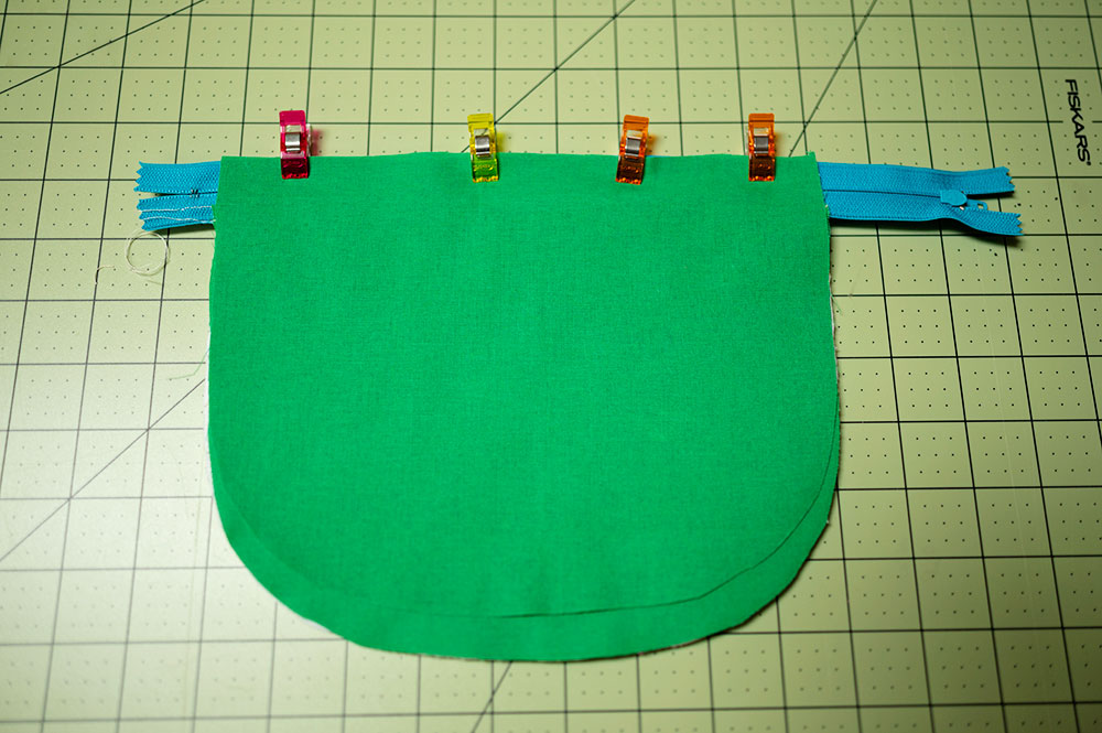 zipper pouch project is clipped together along the top, lined up with the edge of the zipper