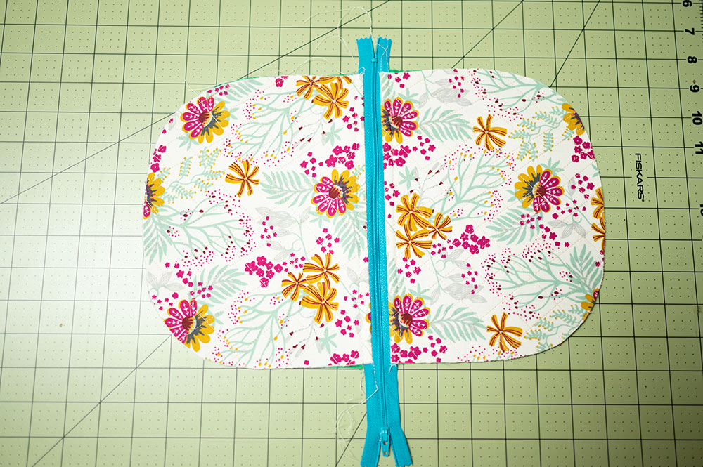 Overhead view of partially sewn quilter zipper pouch showing the top stitch line from the outside side of the project